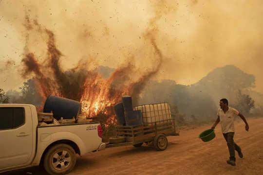 एक स्वयंसेवक 11 सितंबर, 2020 को पोकोन, माटो ग्रोसो राज्य, ब्राज़ील के पास पंतनलाल आर्द्रभूमि में ट्रांसपेंटानेइरा सड़क पर आग लगाने की कोशिश करता है।