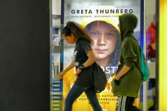 लोग इटली में ग्रेटा थुनबर्ग की किताब के एक पोस्टर के पीछे चलते हैं।