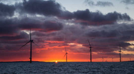 The sun rises behind an offshore wind farm. Image: Aaron via Flickr